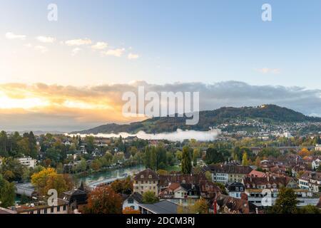 Panorama urbain de Berne et de la montagne Gurten au lever du soleil. Vue sur l'ambiance chaleureuse du matin au lever du soleil et les petits champs de brouillard sur la capitale suisse Berne Banque D'Images