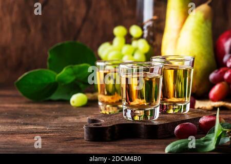 Rakija, raki ou rakia - balkanique de forte boisson alcoolisée de type brandy à base de fruits fermentés, table en bois vintage, encore la vie dans le style rustique, lieu f