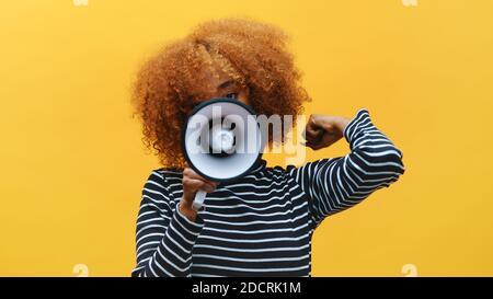 Femme noire afro-américaine aux cheveux bouclés criant dans le haut-parleur. Photo de haute qualité