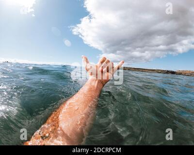 Homme mains dans le surf signe hallo hors du bleu l'eau de l'océan avec la côte et le ciel agréable en arrière-plan - concept de personnes et vacances d'été