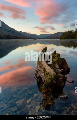 Magnifique lever de soleil rose avec des reflets calmes à Ullswater, dans le Lake District. Banque D'Images