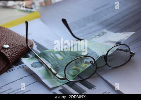 Portefeuille en cuir marron, billet de banque de 100 euros, lunettes et rapport financier. Finance - concept d'entreprise d'analyse des pertes et profits