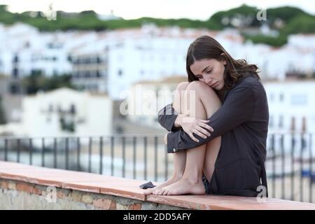 Portrait complet d'un adolescent triste se plaignant assis dessus une corniche dans une ville de plage