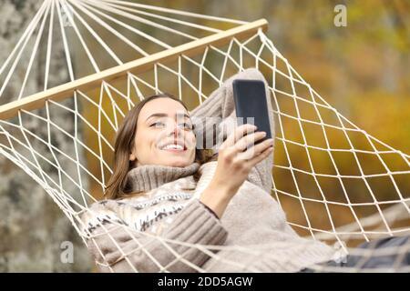 Bonne femme qui vérifie un téléphone portable allongé sur un hamac vacances en automne
