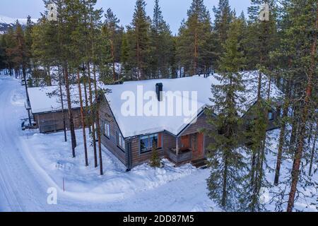 Cabine aérienne en bois dans la forêt reculée, avec bois enneigés et paysage d'arbres en Laponie, Finlande, Europe