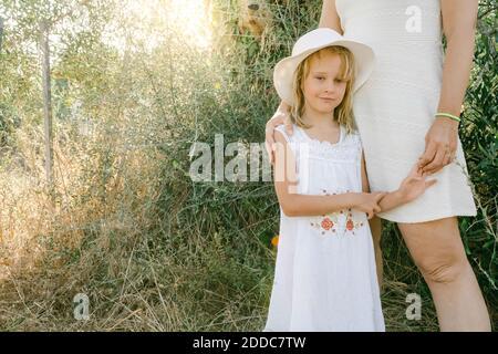 Jolie fille tenant la main de la mère tout en étant debout sur le terrain