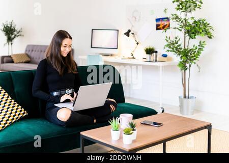 Souriante jeune femme utilisant un ordinateur portable pour bloguer pendant qu'elle est assise sur le canapé à la maison