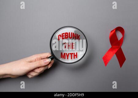La main d'une femme tient une loupe avec du texte. Ruban rouge sur fond gris. Pose à plat. Le concept de la Journée mondiale du sida.