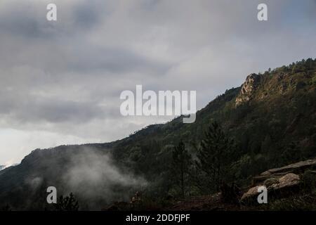 Paysage de montagne sur une journée brumeuse avec des ouvertures de soleil comme le brouillard se soulève