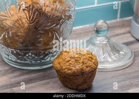 Muffin aux carottes, aux pommes, à la cannelle et aux graines de citrouille sur le comptoir de la cuisine, à côté d'un pot en verre avec muffins