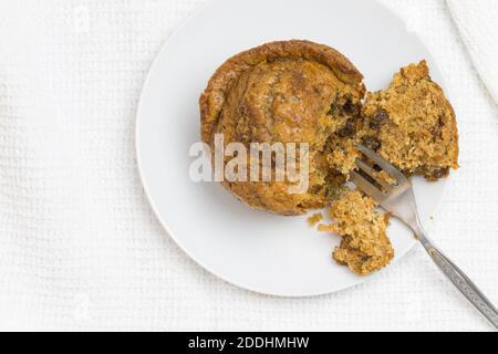 Muffin avec fourchette à gâteau, photo de dessus avec mise au point sélective et espace de copie sur blanc - carotte, pomme, cannelle et raisins secs muffin
