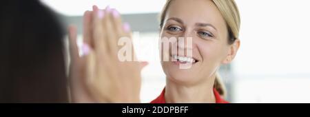 Belle jeune femme en blouson d'affaires rouge donne cinq hauts à un collègue au bureau