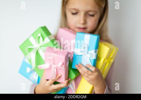 Joyeux enfant recevant présent le jour de la boxe. Petite fille souriante avec cadeau enveloppé. Petit enfant dans un chapeau rose portant un cadeau d'anniversaire isolé sur