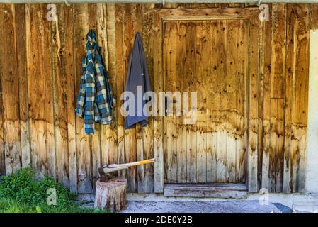 Deux haches en bois coincées dans le coffre à hacher en bois. En arrière-plan, un mur en bois de la maison et deux vêtements de travail accrochés à un crochet.
