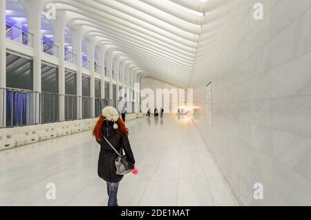 REDHEAD Femme marchant à travers un World Trade Center au rez-de-chaussée. Belle décoration et architecture blanche minimaliste. Manhattan, New York, États-Unis