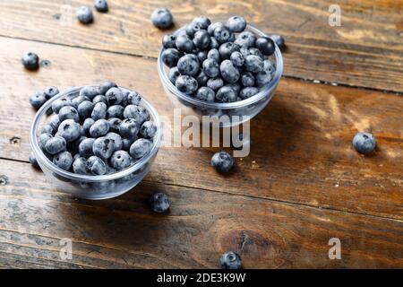 Bleuets frais dans un bol en verre et éparpillés sur une table en bois. Aliments contenant des antioxydants. Une alimentation saine.