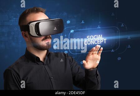 Homme d'affaires regardant à travers les lunettes de réalité virtuelle avec inscription DE CONCEPT SOCIAL, concept de réseautage social Banque D'Images