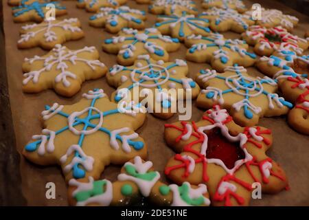 Plateaux de biscuits de Noël décorés de glaçage coloré, certains d'entre eux avec vitraux