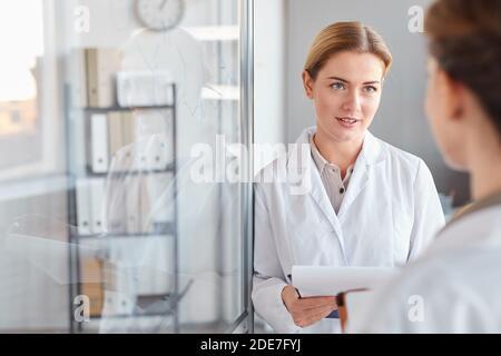 Portrait à la taille de deux femmes scientifiques parlant et tenant la planchette à pince tout en faisant des recherches en laboratoire médical, l'espace de copie