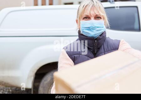 Messager de colis avec masque de visage extérieur devant elle le véhicule livre le colis