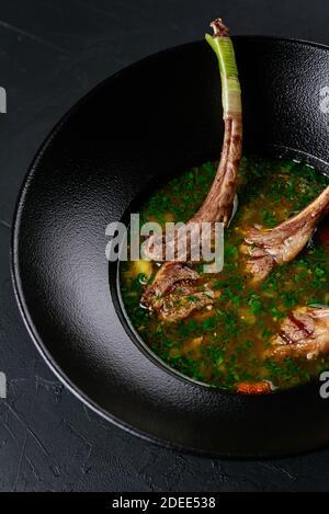 soupe de viande avec un carré d'agneau sur un noir arrière-plan