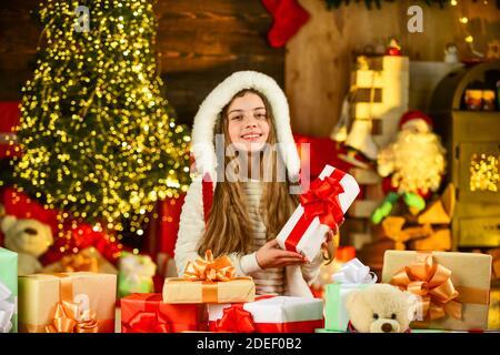 Le meilleur cadeau. Vacances et vacances d'hiver. Enfant avec cadeau. Temps libre et joie. Enfant en costume de père noël. Matin avant Noël. Jolie petite fille avec des cadeaux. Les enfants apprécient les vacances. Banque D'Images