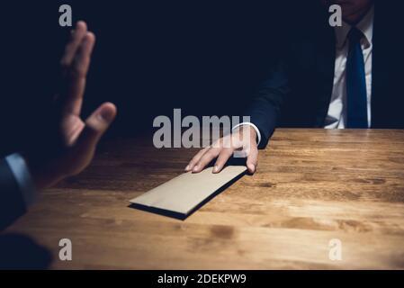 Homme d'affaires rejetant de l'argent dans l'enveloppe fournie par son partenaire dans une salle privée sombre - concept anti-corruption