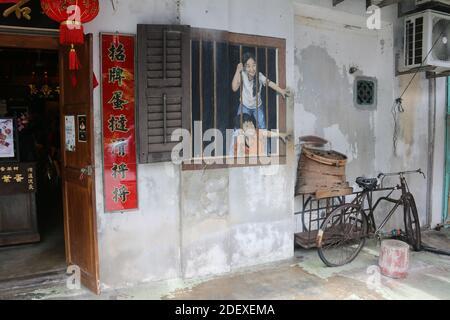 GEORGETO, MALAISIE - 28 novembre 2020: Vélo vide devant l'art de la rue: Un garçon et une fille qui atteint par une fenêtre: 'Je veux Bao' par E. Zacharevic, Georgeto