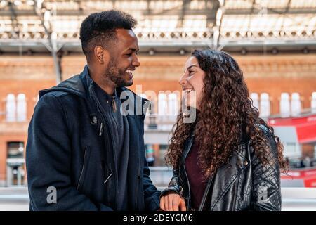 Photo de stock du moment heureux de couple interracial d'amoureux regardant les uns les autres. Ils sont à Madrid