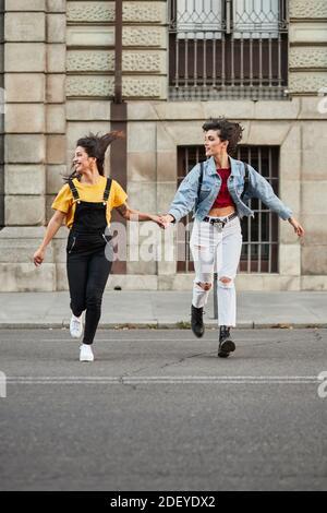 Photo de stock de deux adolescentes qui descendent dans la rue et tiennent les mains. Ils portent un tissu décontracté et des lunettes de soleil.