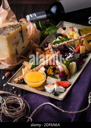 Assiette de fromage servie avec des raisins et des noix. Assortiment de fromages camembert, brie, parmesan bleu, chèvre aux raisins, bâtonnets de gressins, noix de cajou, miel et an