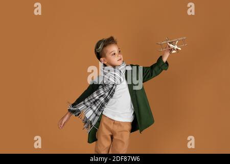 enfant garçon heureux jouant avec un avion en bois jouet sur fond de studio. enfant rêve de voyager