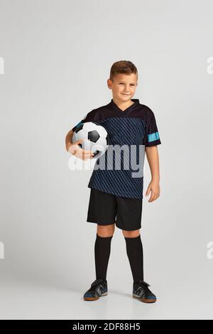 petit garçon joueur de football en uniforme tenant le ballon sur fond de studio. enfant rêve de devenir joueur de football.