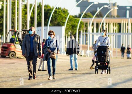 Huelva, Espagne - 3 décembre 2020: Couple marchant sur la promenade de Huelva au coucher du soleil, portant des masques protecteurs ou médicaux pendant l'état d'alarme et qu