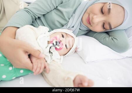 Bébé et mère à la maison au lit, famille heureuse