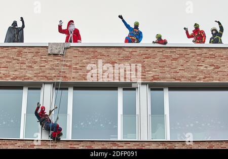 Hambourg, Allemagne. 06e décembre 2020. Les sauveteurs en hauteur des pompiers, vêtus comme le Père Noël, Darth Vader, Superman et Spiderman, entre autres, brandillent sur le toit de l'hôpital universitaire pour enfants Eppendorf (UKE). Les pompiers ont surpris les petits patients le jour de Saint-Nicolas en descendant la façade de l'UKE pour enfants en costume. Credit: Georg Wendt/dpa/Alay Live News