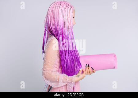 Fille élégante, cheveux longs roses dans les tresses, portant une robe et tapis de yoga sur un fond blanc. Photo de profil.