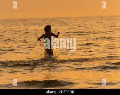 fille éclaboussant dans l'eau de mer