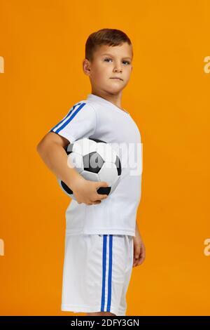 petit garçon joueur de football en uniforme tenant le ballon sur fond jaune. enfant rêve de devenir joueur de football.