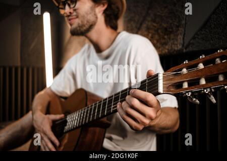Gros plan jeune musicien masculin attrayant jouant avec confiance à la guitare en studio d'enregistrement