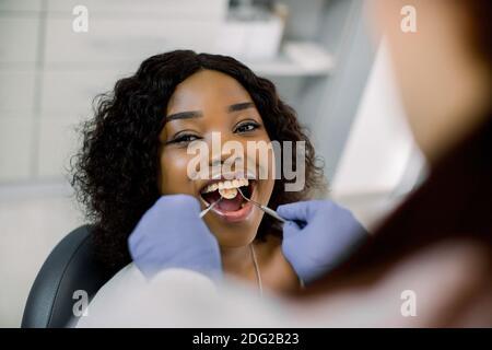 Gros plan de jeune belle femme afro souriante avec de belles dents blanches, assise dans une chaise dentaire, tandis que la femme dentiste guérit ses dents. Dentiste