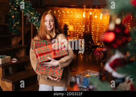 Portrait de jeune belle femme tenant une boîte avec des cadeaux de Noël enveloppés dans du papier artisanal.