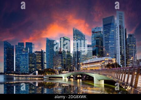 Vue imprenable sur le Merlion Park avec les gratte-ciel de Singapour en arrière-plan pendant un magnifique et spectaculaire coucher de soleil.