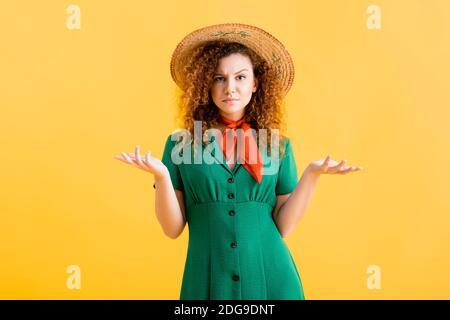 confusion jeune femme en chapeau de paille et robe verte gestante sur jaune