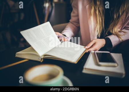Entreprise, concept d'éducation. Femme travaillant à l'extérieur au café. Gros plan femme caucasienne main sur table en bois à l'intérieur du café