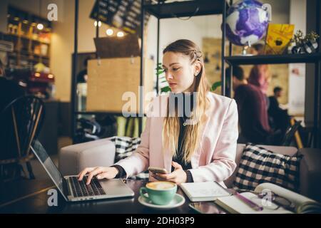 Femme d'affaires indépendante travaillant sur ordinateur portable et téléphone portable, avec une tasse de café sur table en bois dans café café café