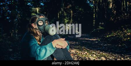 Fille avec masque à gaz dans la forêt au coucher du soleil