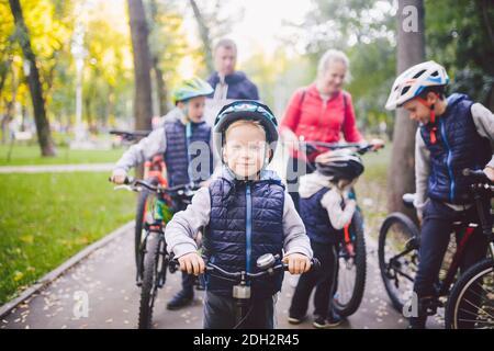 Thème vacances sportives familiales dans le parc dans la nature. Grande famille caucasienne sympathique de six personnes à vélo de montagne équitation dans la forêt. Chil