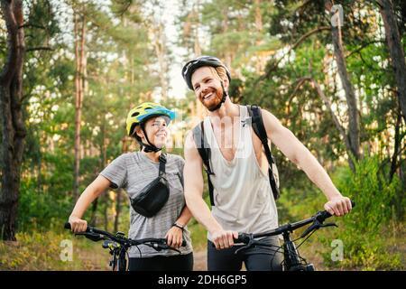Vélo. Piste VTT MTB en couple. Activités sportives en plein air. Couple avec vélos dans la forêt. Ensemble sur la course à vélo en cou