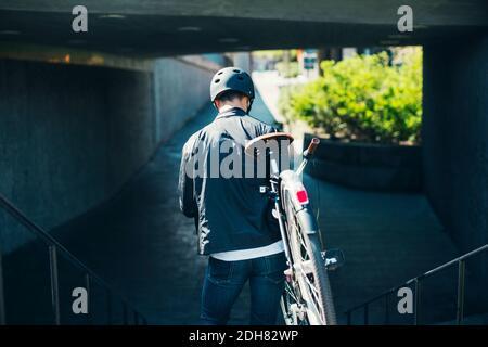 Vue arrière d'un homme d'affaires transportant un vélo tout en descendant des marches